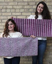 Sylvia & Miranda with bolts of fabric