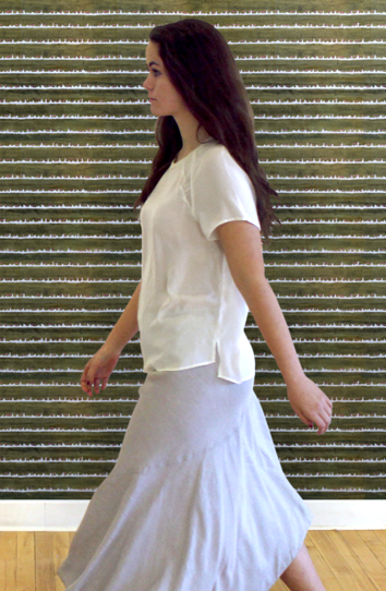 sylvia walking in front of a green deckledot wall